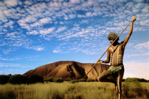 Aboriginal hunter in outback at sunset.