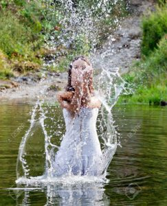 Young-woman-in-white-dress-in-a-river