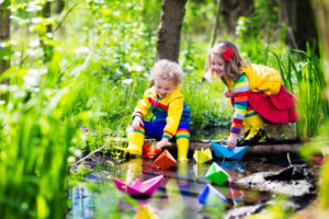 children-play-with-colorful-paper-boats-in-a-small-river-on-a-sunny-spring-day-kids-playing