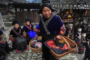 """An ethnic Miao woman carries baskets of hand embroideries to show guests, on the first day of the Guzang Festival in Leishan county, where most of the Miao ethnic group live, southeast Guizhou province, November 26, 2012. Guzang Festival, during which the Miao ethnic minority people commemorate their ancestors once every 13 years, is one of the biggest traditional festivals for the Miao ethnic minority people. """"Gu"""" literally means """"drum"""", and """"zang"""" means """"to bury"""". The complicated rites which take three years to complete consist of a series of great ceremonies, including the Zhaolong (inviting the dragon), Xinggu (awakening the drum), Yinggu (welcoming the drum), Shenniu (inspecting the cattle), and the white drum ritual, which is a significant sacrifice marking the end of the festival. The Miao believe wooden drums made of maple trees are where their ancestors' souls rest, so they gather under the holy maple and communicate with their ancestors through drumming and dancing, local media reported. Picture taken November 26, 2012. REUTERS/Sheng Li (CHINA - Tags: SOCIETY ANNIVERSARY)"""